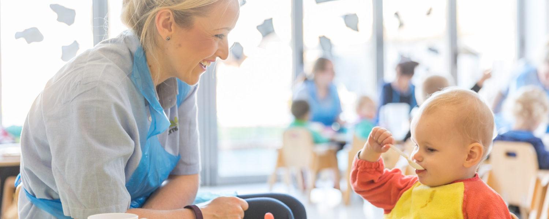 Nursery nurse feeding child